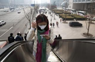 A woman wears a mask during a day of heavy pollution in Beijing, 7 March
