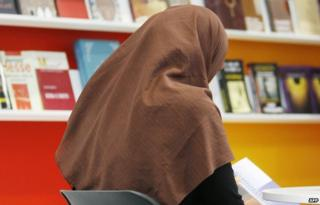 A veiled woman reads a book in front of shelves at the stand of Macedonia at the Leipzig Book Fair, 18 March 2010