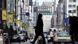 Pedestrians cross a street of the Ginza shopping district in Tokyo.
