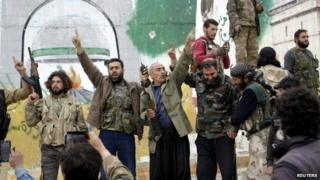 Rebel fighters celebrate at the Mihrab roundabout in the Idlib city centre, after they took control of the area, 28 March 2015.