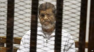 Mohammed Morsi inside a dock at a court in Cairo, Egypt (8 May 2014)