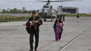 An Indian Air Force person walks carrying a Nepalese child, wounded in Saturday's earthquake, to a waiting ambulance as the mother follows after they were evacuated from a remote area at the airport in Kathmandu, Nepal, Monday, April 27, 2015