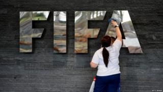 Woman wiping the Fifa logo