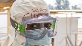 A health care worker wearing virus protective gear before entering a high risk zone at an Ebola virus clinic operated by the International Medical Corps in Makeni, Sierra Leone 2 March 2015