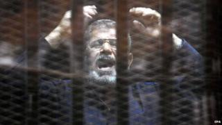 Mohammed Morsi stands inside a glassed-in defendant's cage (16 June 2015)
