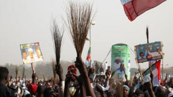 Supporters of Muhammadu Buhari holding up brooms at a rally in Nigeria - 2015