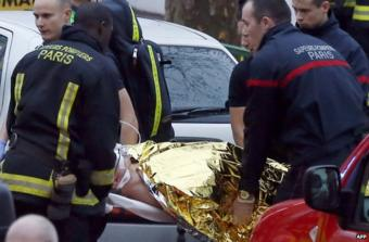Rescue service workers and firefighters evacuate an injured person on a stretcher near the site of a shooting in Montrouge, south of Paris, 8 January