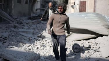 ゴウタ東部で政府軍の空爆を受けたとされる場所を歩く男性(14日)