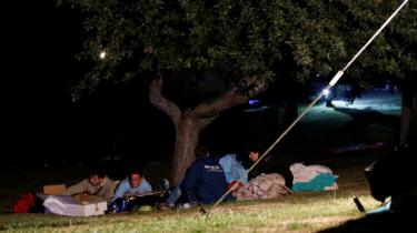 People cover themselves with blankets as they prepare to spend the night in the open following an earthquake in Amatrice