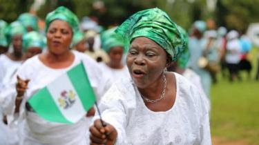 A woman raises the Nigerian flag as she participates in a parade to commemorate Nigeria's 55th independence day in Lagos, Nigeria - 1 October 2015