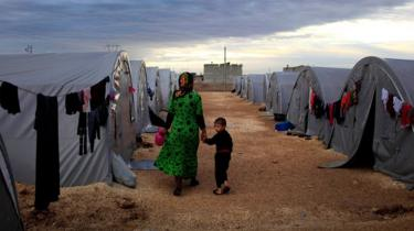 A Syrian Kurdish refugee mother and son from Kobane walk beside their tent in a camp in the south-eastern Turkish town of Suruc, on the Turkish-Syrian border (19 October 2014)