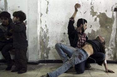 A man gives medical assistance to an injured man after what activists said was an air strike by government forces the Duma district of Damascus, Syria (2 February 2015)