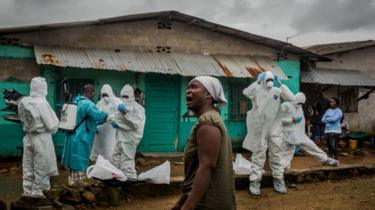 A relative grieves as a Red Cross burial team prepares to remove the body of an Ebola victim in Liberia