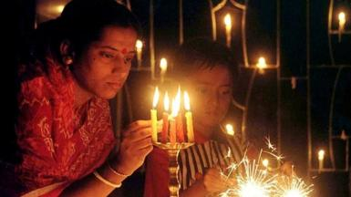 Namita Biswas, a Bengali housewife, lights candles as her son lights sparklers during Diwali in Calcutta, 26 October 2000