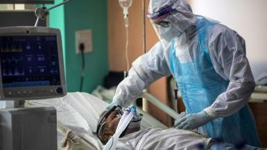 A medical staff member wearing Personal Protective Equipment (PPE) suit looks after a Covid-19 patient at the Intensive Care Unit of the Sharda Hospital, in Greater Noida near Delhi