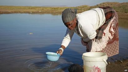 Woman collects water in Qunu