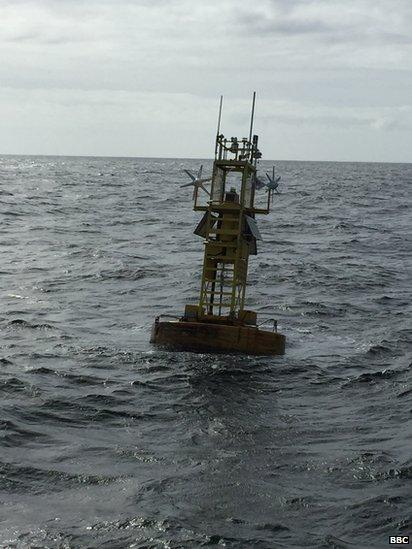 Weather data collection equipment floating in the sea under a cloudy sky