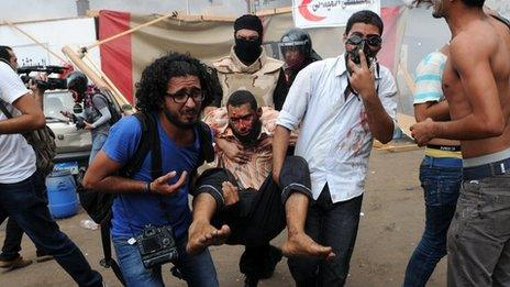 People carry an injured protester at Nahda Square in Cairo during clashes between supporters of Egypt's ousted president Mohamed Morsi and riot police on August 14, 2013