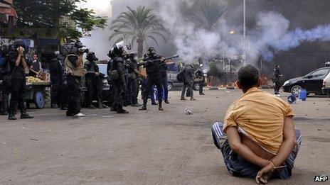A handcuffed protester sits on the ground as Egyptian security forces move in to disperse supporters of Egypt's ousted president Mohamed Morsi in Cairo's Nahda Square on 14 August 2013.