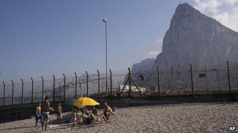 People play on the beach next to a separation fence between Gibraltar, in the background, and Spain in La Linea de la Concepcion