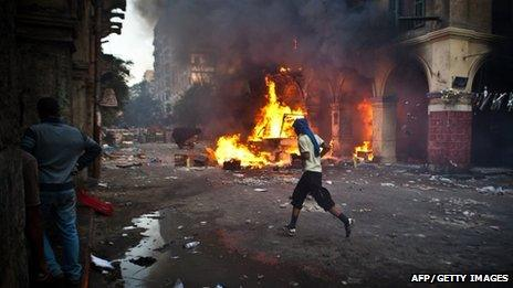 A supporter of the Muslim Brotherhood runs past a burning vehicle in Cairo