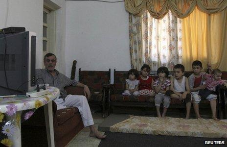 A family of Syrian refugees watch television