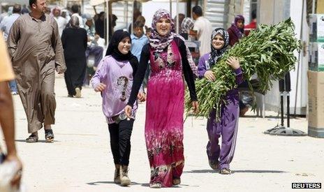 Syrian refugees walk on the main market street at Al-Zaatri refugee camp