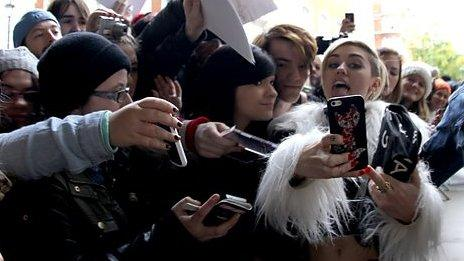 Miley Cyrus poses with fans