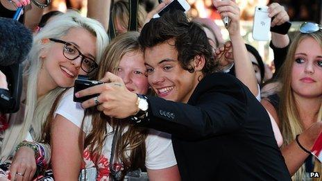 Harry Styles posing for picture with fans