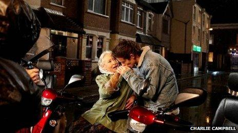 Louis Tomlinson kissing an elderly lady
