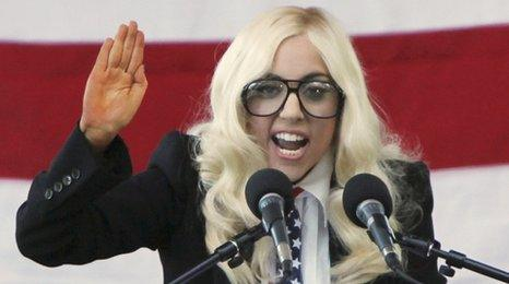 Lady Gaga dressed in blonde wig and wearing suit speaking at a rally