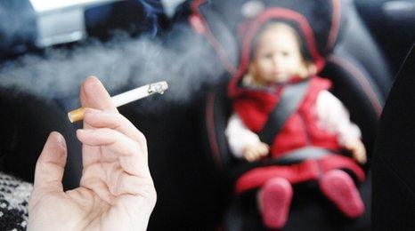 Man smoking in car with child