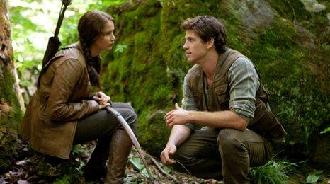 Jennifer Lawrence as Katniss Everdeen and Liam Hemsworth as Gale Hawthorne