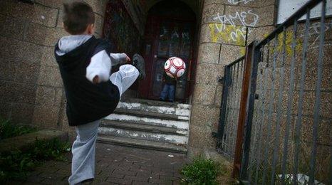 child kicking football