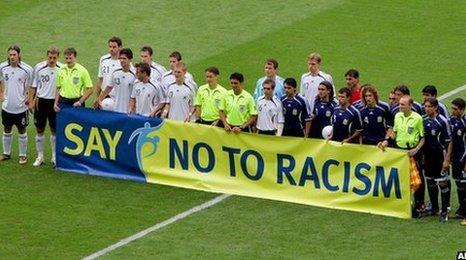 Germany and Argentina players in front of anti-racism banner