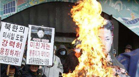 Protestors burn an effigy of the North Korean leader Kim Jong-un after his country's missile launch