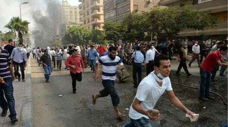 Egyptian pro-Morsi protesters run from police in a street leading to Rabaa al-Adawiya protest camp in Cairo on August 14, 2013