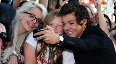 Harry Styles takes a selfie with fans