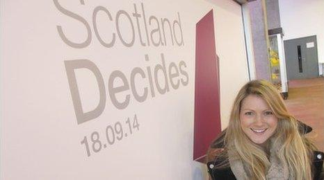Shona in front of a Scotland Decides sign