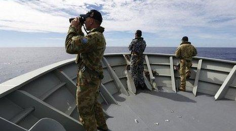 This handout photo taken on 7 April 2014 and released on 9 April 2014 by Australian Defence shows Gunner Richard Brown (L) of Transit Security Element on the lookout on the forecastle of HMAS Perth in the search for missing Malaysia Airlines flight MH370 in the southern Indian Ocean