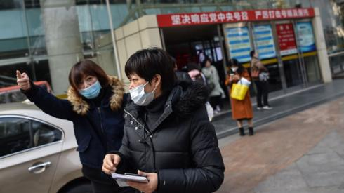 Two women wear protective masks in front of a hospital in Shanghai
