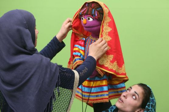 An Afghan puppeteer adjusts a scarf on Zari