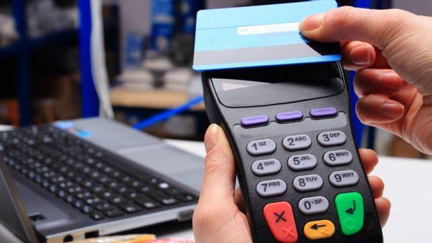 Una persona pasando una tarjeta por un terminal de pago. Al fondo, una laptop