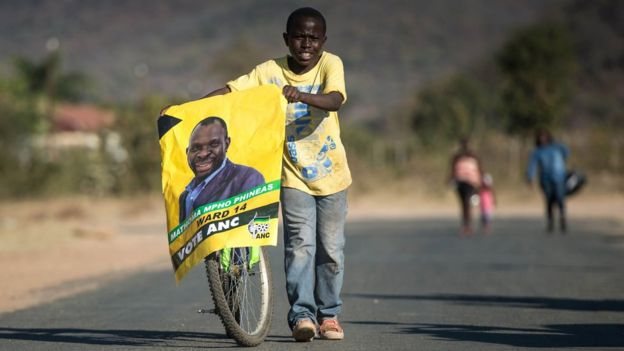 A boy pushes his bicycle as he holds a candidate poster of the South African ruling party African National Congress on the eve of South African Municipal elections on August 02, 2016 in Vuwani