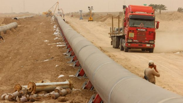 Workers set up a natural gas pipeline during a dust storm at Iraq's border with Iran in Basra