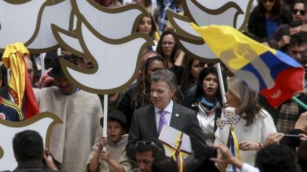 Juan Manuel Santos rodeado de una multitud con pancartas en forma de palomas de la paz.