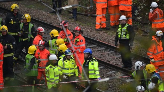 Members of London Fire Brigade and Police officers walk the tracks