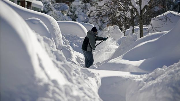 A resident shovels snow away from the entrance to his home in Union City, New Jersey, across the Hudson River from Midtown Manhattan, after the second-biggest winter storm in New York history, January 24, 2016.