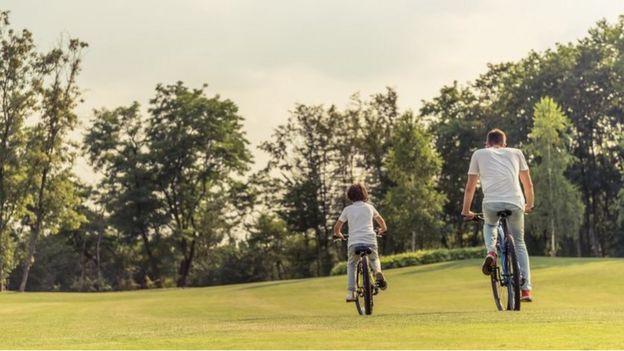 Un hombre y un niño en bicicleta en un parque