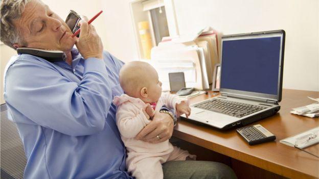 Padre con bebé, hablando por teléfono